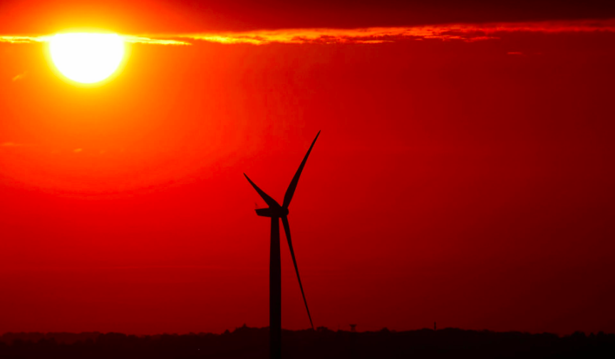 The sun rises behind an electric power windmill in Halle, Belgium September 11, 2019. REUTERS/Yves H