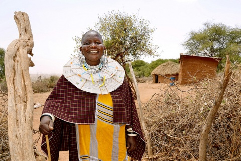 Mama Neema stands at the entrance of her traditional boma (homestead) where she built three houses for her family in Kimokouwa village in Arusha, Tanzania UN WOMEN