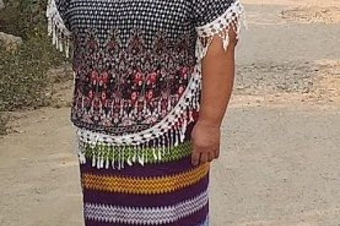Daw Nang Nwe stands on dirt road outside her shop