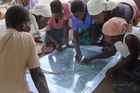 •	Women in Burlobo community, Northern Uganda, use a satellite map to draw sketch maps of their land, with the help of  the Land and Equity Movement in Uganda (LEMU).