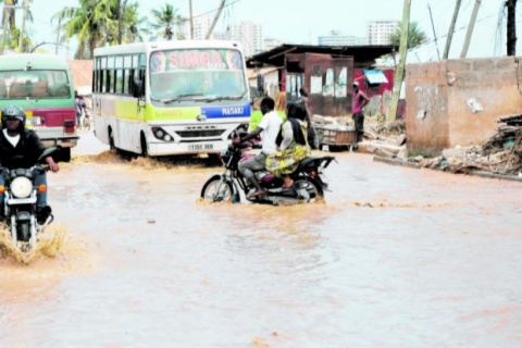 Motorcycle riders and commuter buses cross at the flooded section of Kigogo Road in Dar es Salaam following the heavy rainfall that pounded the city recently. PHOTO | MICHAEL MATEMANGA